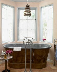 aged to perfection Antiques and patina dominate the decor in designer Penelope Bianchi's Santa Barbara home. One of her favorite features is this 1860s zinc-lined copper tub, surrounded by a trio of windows.