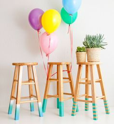 Use spray paint and painter's tape to DIY these color-dipped bar stools.