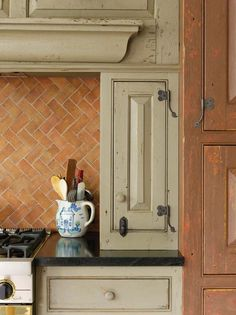 """""""A custom finish and blacksmith-made hardware complete the period style of cabinets and woodwork; counters are soapstone."""""""