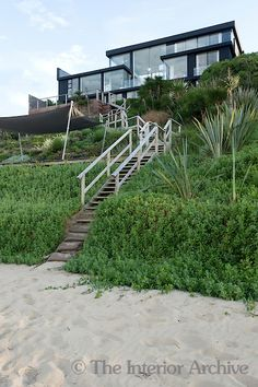 A set of wooden steps lead up to the house from the beach