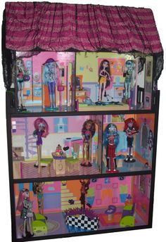 DIY haunted house for my tween's Monster High dolls: bought a used little girl dollhouse, painted wood trim black, added monster stickers inside + spooky cloth to roof
