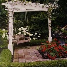 carve out a little quiet space in the corner of your backyard for a pergola painted white, a brick path and a swing.  perfect