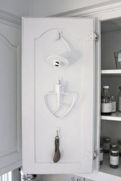 Hang the everyday baking attachments for my KitchenAid mixer and measuring spoons with Command Hooks on back of cupboard.