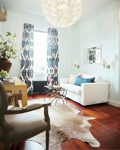 Living Room Photo - A white couch, blue ikat curtains, and nesting tables in a living space