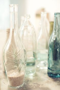 Recycled glass bottles look pretty filled with sand—or can double as vases too