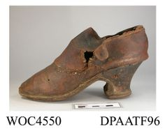 1710 - 1730  shoe, brown leather, latchet tied over high broad tongue, straight side and rear seams, unlined, high curved and waisted sturdy wooden heel with woodworm damage, originally leather covered, edges outlined with double line of cream stitching, straight leather sole, repairs to upper, approximate length overall 200mm, approximate heel height 65mm, approximate width of sole 80mm, c1710-1730 HMCMS:WOC4550 Hampshire Museums  *Wormwood damage indicates Continental origin