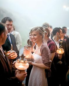 Bridesmaids carrying glowing lanterns instead of floral bouquets...compliments of martha stewart.