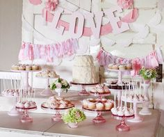 A lovely wall fixture of pink ribbons acts as a backdrop for this spring wedding dessert table.