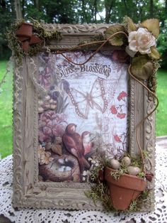 Vicki Chrisman shows how to age a dollar store frame and create a little piece of art using layers of our Bird & Blossom Creative Scraps, twigs, fabric flowers & leaves, moss, broken terracotta, buttons, eggs, and gems.