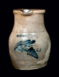 "Price Realized: $ 201.25 Half-Gallon Cobalt-Decorated Stoneware Pitcher, Stamped ""COWDEN & WILCOX,"" Harrisburg, PA origin, circa 1875, ovoid pitcher with tall flaring collar and tooled rim, decorated with a hanging floral motif featuring a conical blossom. Top-to-bottom crack on front. Small rim chip and small spout chip. Staining to surface."