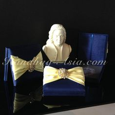 Midnight blue silk invitation box for weddinginvitations with wide yellow ribbon and brooch