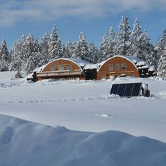 Lee from of Idaho shared this photo of his earth-sheltered home surrounded with tire bales that act as retaining walls and insulation. In the foreground are four 80 watt solar panels that power the well pump.