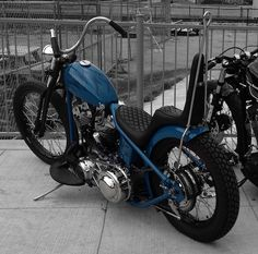 Deep blue shovelhead hardtail custom with diamond stitch king/queen seat, black rims and curved handlebars