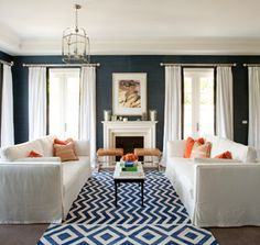 navy blue walls, white and coral living room
