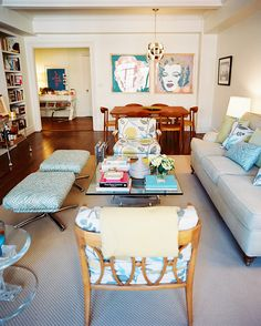 Living Room Photo - A pair of ottomans, floral-print chairs, and a roll-arm couch surrounding a glass coffee table