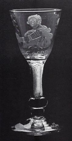 The composite stem of this glass consists of a multi-spiral air twist set into a squat inverted baluster. The round funnel bowl is engraved with a portrait and the words KING OF PRUSSIA. this is Frederick the Great, engraved during his mid-18th century period of popularity with the British public, when his portrait and praises were recorded on Worcester and other porcelain as well as on glass.