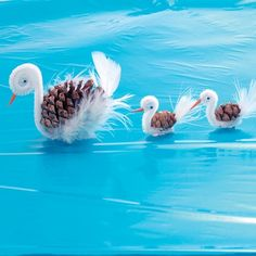 Could these swans be a decoration in a tiny pond in a tiny garden?  For the beak, color the end of a toothpick with orange marker, cut it off, and use tacky glue to attach it to the head coil. Glue on a set of googly eyes. To finish, glue a pinecone to the pipe cleaner base, then glue feathers to the pinecone.