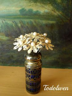 Tiny book page flowers in a saltshaker vase