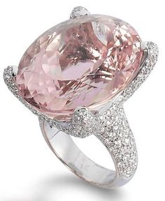 A kunzite and diamond ring.   Set with an oval kunzite, to the claws and shoulders pavé-set with round brilliant-cut diamonds, mounted in 18k white gold, the kunzite estimated to weigh approximately 54.70 carats, the diamonds estimated to weigh approximately 3.80 carats in total, ring size 6½. Bonhams.