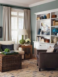 Like the paint color - style expert Cameron MacNeil created a varied and interesting display on the bookshelves, using an oil painting of an urban landscape as his colour inspiration. Shapely pottery and a punchy turquoise globe mix with more muted tones in the books and wood accessories.