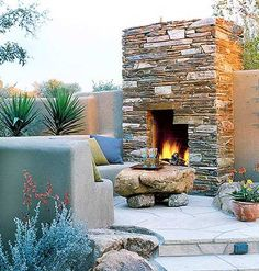 A patio with a stone fireplace and stone coffee table