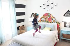 love the black and white horizontal stripes along with the bright colored fabric headboard