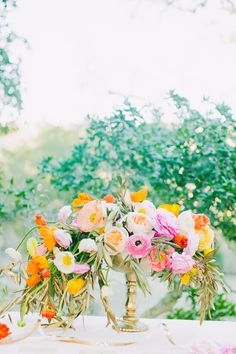 Wedding Centerpiece: on http://www.StyleMePretty.com/2014/04/07/cheerful-spring-inspiration-shoot/ poppies, ranunculus, garden roses, jasmine vines by VoFloralDesign -- Photography: AvecLamourPhotography.com
