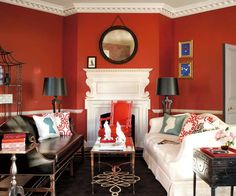 Saffron walls lend a traditional cohesion to eclectic furnishings. | Cochineal Red CW-330 (walls), Capitol White CW-10 (trim), Timson Sand CW-140 (ceiling), @Benjamin Moore Colonial Williamsburg collection