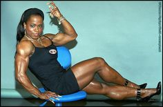 IFBB Pro Female Bodybuilder Kim Harris flexing a bicep and posing her muscular calves for WPWMAX!