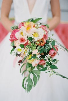Bouquet of poppies, ranunculuses, garden roses, tulips, veronica, mock orange, peonies, and Queen Anne's lace | Brides.com