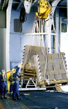 Check out the heavy-lifting cranes hoisting supplies for sailors on USS Theodore Roosevelt's hangar bay.