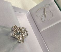 Detail picture of our monogram embroidered silk wedding invitation box featuring rhinestone crystal brooch.
