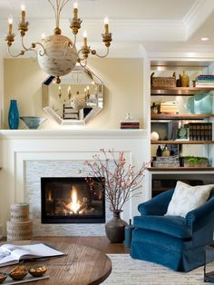The fireplace is made a focal point in the living room by a tile surround and oversized molding. A beveled mirror adds a touch of glamour to the room and reflects the vintage-inspired chandelier.  Design by Candice Olson