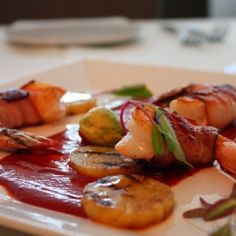 Bacon-wrapped shrimp with a garlicky Chipotle sauce, garnished with ...