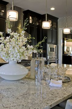 Check out those dark cabinets! #ModelHome ..Love the granite and wallpaper together with the light touch of white and glass accessories and the graceful lighting choices. The perfectly well put together room.