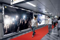An interactive billboard by Nikon in a subway station in Seoul. A surge of flashing camera lights are triggered when people walk by.