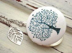 Delicate Tree Of Life - soft grey-blue, enameled locket necklace with silver leaf charm and long necklace. $23.90, via Etsy.