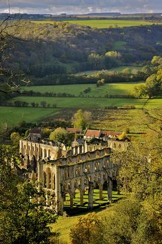 ~Rievaulx Abbey (pronounced ree-voh) is a former Cistercian abbey headed by the Abbot of Rievaulx. It is located in Rievaulx, near Helmsley in the North York Moors National Park, North Yorkshire, England. It was one of the wealthiest abbeys in England and was dissolved by Henry VIII of England in 1538. Its ruins are a tourist attraction.~