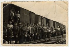 Jewish men in a Hungarian forced labor battalion stand inside and along side a train. Friday, June 18, 1943.