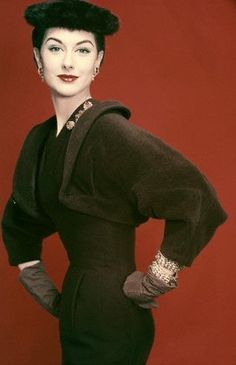 Vogue. Nancy Berg is wearing fitted wool dress with short bolero jacket by Adele Simpson, fur beret by Superb, photo by Erwin Blumenfeld, c.1953