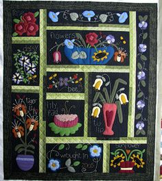 Wool applique quilt with flowers and embroidery.  Blanket stitching around the applique.  If anyone recognizes this pattern please let us know.