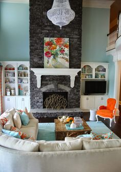 Love the contrast of the dark stone, cream mantel and colorful art