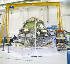 Inside the Operations and Checkout Building high bay at NASA's Kennedy Space Center, the Orion crew module is positioned on a special portable test chamber and prepared for a multi-point random vibration test. (NASA.gov image)