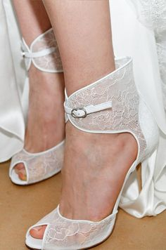 A pair of white lace, peep-toe wedding shoes from the Monique Lhuillier Fall 2013 bridal collection feature a delicate white strap.