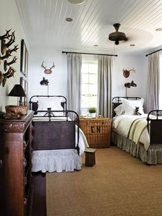 rustic cottage decor with planked ceilings, deer antlers, metal bedframes, and those light fixtures are the perfect rustic touch.