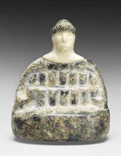 A Bactrian composite stone seated female figure  Circa late 3rd - early 2nd Millennium B.C.  The body and hair made of chlorite, wearing the typical woven heavy cloak, the separately made white stone head set into the recess on its neck, with large carved almond-shaped eyes and small round ears, 3¼in (8.5cm) high