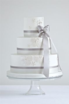 Silver and white tiered wedding cake with a bow