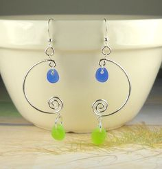 """Beautiful new design with a funky edge! These spiral hoops are all Sterling Silver. I have dangled beautiful and rare cobalt blue and lime green sea glass gems that I found in Northern California. These are large dangling earrings for those of you ocean-lovers who like to make a statement! I love them myself! each one measures 1"""" wide by 2 3/4"""" in length. All of the components are Sterling Silver.Like all my jewelry, this necklace comes beautifully-boxed with pretty ri..."""
