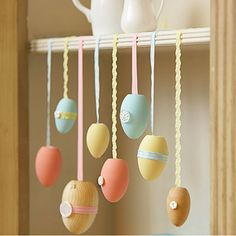 Bring some spring to a bookcase. On wooden eggs, brush acrylic paint and let dry, then trim with buttons and bits of ribbon. To hang, affix one end of ribbon to egg with hot glue; tape other end to shelf. #Easter