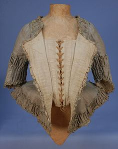 Open front if a PLAID SILK CARACO JACKET, c. 1770. Narrow sea green vertical stripe over cream and tan horizontal bands, open neck, short angled sleeve, pleated peplum angled at front, all trimmed in wide self furbelows, looped silk cord and tiny tassels, lined in linen with adjustable lacing closure and front stays. B-33, W-24, L-21. (Lace modern) whitakerauction's Photos | SmugMug